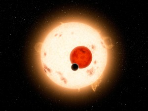 Artistic view of the components of the ternary system Kepler-16 in transit. The late-K star (large and orange) and M-dwarf star (reddish and smaller) and the exoplanet (dark) are shown to their relative size at the time of a transit. Sunspot activity as seen on Kepler-16A was indeed detected by Kepler.